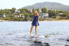 Young woman standing on the stone in the sea and laughing Stock Photography