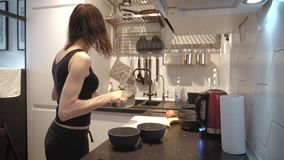 Young woman standing by the stove in the kitchen and preparing breakfast for the family, lifestyle video. Everyday stock video