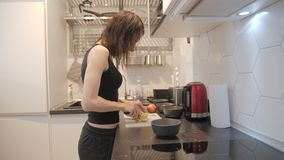 Young woman standing by the stove in the kitchen and preparing breakfast for the family, lifestyle video. Everyday stock video footage