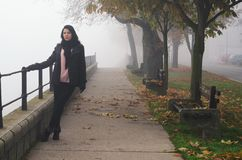 Young woman standing on the street on foggy autumn day royalty free stock photography