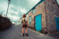 Young woman standing in street outside old house Stock Images