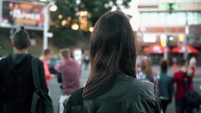 Young woman standing on street, preparing cross road at traffic lights, hair fluttering in the wind. Back view. Slow mo. Young beautiful brunette woman in black stock video footage