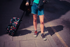 Young woman standing in the street with a suitcase Royalty Free Stock Photography