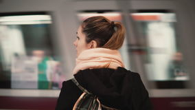 Young woman standing in the subway platform against the background of passing train. Girl waiting metro to go to job. Young woman standing in the subway stock video footage