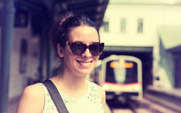 Young woman standing on subway platform waiting approaching train Stock Photography
