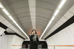 Young woman standing on a subway station, waiting for metro and Stock Images