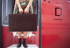 Young woman standing with suitcase on train Royalty Free Stock Photography