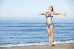 Young Woman Standing On Summer Beach Stock Photo