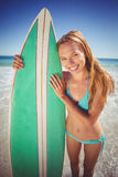 Young woman standing with surfboard on beach Royalty Free Stock Images