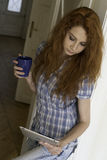 Young woman standing with a tablet and a mug Stock Images