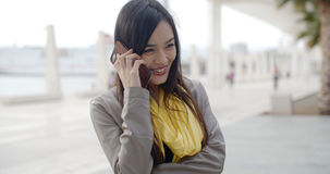 Young woman standing talking on her mobile phone Stock Photo