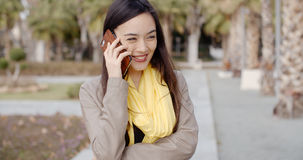Young woman standing talking on her mobile phone Royalty Free Stock Photos