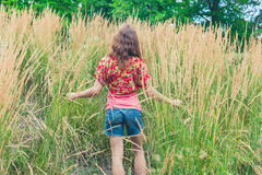 Young woman standing in tall grass Stock Photography