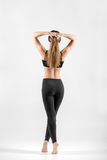 Young woman standing on tiptoes holding her hair in arms Royalty Free Stock Photography