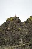 Young woman standing on the top of cliff. With putting her hands up Stock Photo