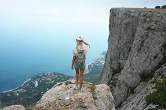Young woman on top of mountain. Young woman standing on top of mountain against sea at cloudy weather. Back view Royalty Free Stock Images