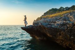 Young woman standing on the top of rock and looking at the seashore and sunset in Si chang island.  Stock Image