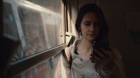Young woman standing in the train and using smartphone. Attractive girl chatting with friends, browse the Internet. Young woman standing in the train and using stock video