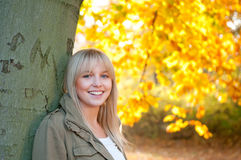 Young woman standing on a tree. In autumn park stock images