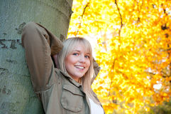 Young woman standing on a tree. In autumn park royalty free stock photo