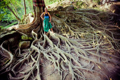 Young woman standing on the tree roots Stock Photography