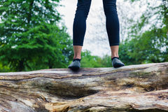 Young woman standing on a tree trunk in park Stock Photography