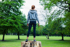 Young woman standing on a tree trunk in park Stock Photo