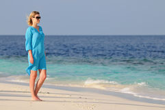 Young woman standing on a tropical beach Stock Image