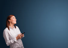 Young woman standing and typing on her phone with copy space Royalty Free Stock Images