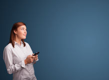 Young woman standing and typing on her phone with copy space Stock Image