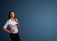 Young woman standing and typing on her phone with copy space Royalty Free Stock Photography