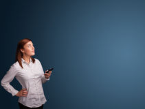Young woman standing and typing on her phone with copy space Royalty Free Stock Photos