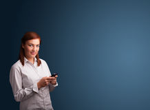 Young woman standing and typing on her phone with copy space Royalty Free Stock Image