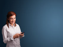 Young woman standing and typing on her phone with copy space Stock Images
