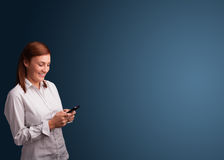 Young woman standing and typing on her phone with copy space Royalty Free Stock Photo