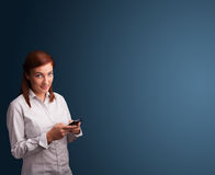 Young woman standing and typing on her phone Stock Photo
