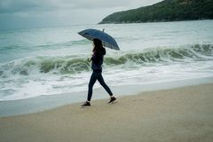 Young woman standing with an umbrella in front sea in winter or. Autumn Royalty Free Stock Photos