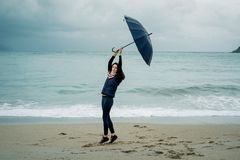 Young woman standing with an umbrella in front sea in winter or. Autumn Stock Photography