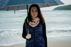 Young woman standing with an umbrella in front sea in winter or. Autumn Royalty Free Stock Photo