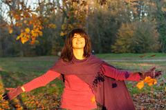 Young Woman Standing Under Falling Leaves Royalty Free Stock Photo