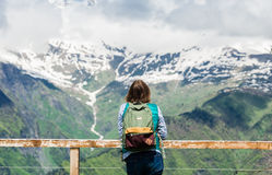 Young woman is standing at viewpoint and looking beautiful mountain landscape. Hiking female tourist with backpack Stock Photos
