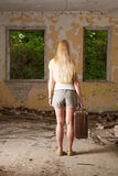 Young woman standing with vintage suitcase. In abandoned building Royalty Free Stock Images