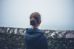 Young woman standing by wall in fog Royalty Free Stock Image