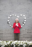 Young woman standing on wall with heart shaped snow balls Stock Photos