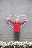 Young woman standing on wall with heart shaped snow balls Royalty Free Stock Photos