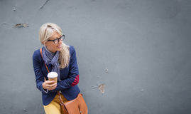 Young woman standing at the wall outdoors and holding a cup of coffee. Stock Photos