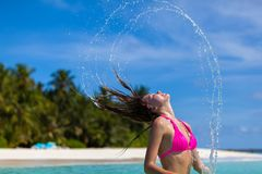 Young woman is standing in the water. And throwing her hair back Royalty Free Stock Photos