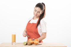 Young woman standing wearing apron cooking, cutting fruit on a board Stock Photos
