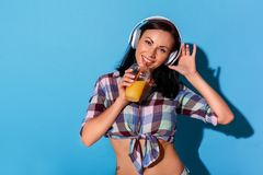 Freestyle. Woman in headphones with bare belly standing isolated on blue wall with drinking smoothie listening to music royalty free stock photography