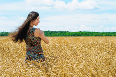 Young woman standing in a wheat cereals field Royalty Free Stock Photography